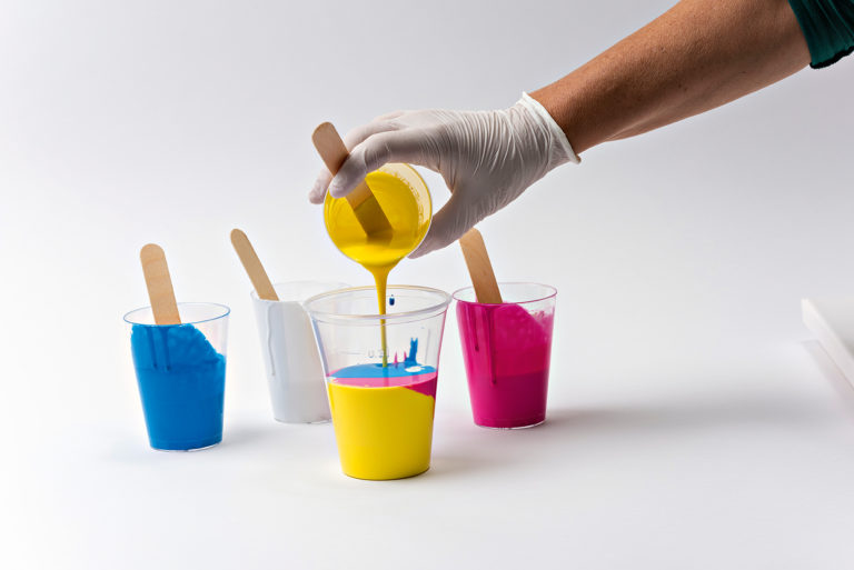 Farbe wird in einen Plastikbecher gegossen.