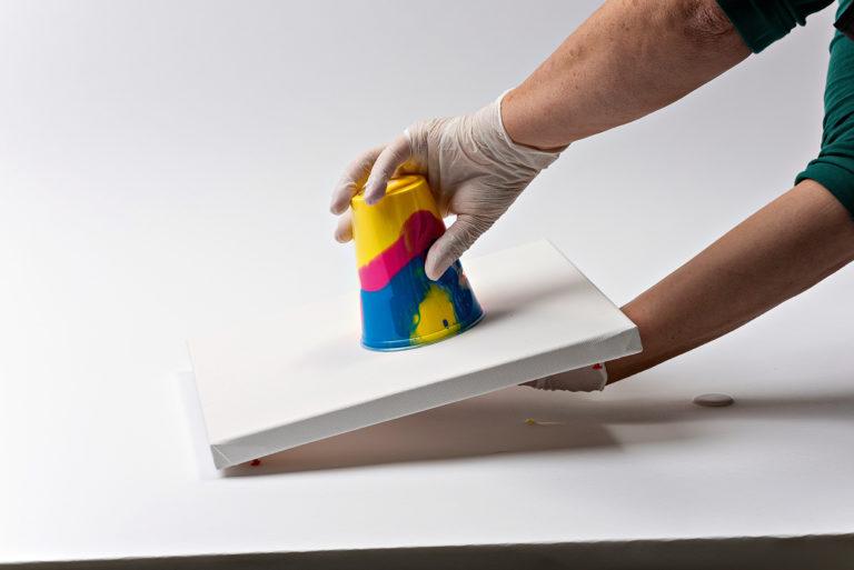 Die Farbe wird mit dem Becher auf dem Keilrahmen aufgesetzt.