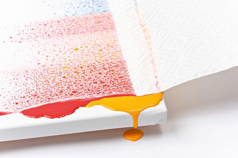 Ein Papier wird über die Farbe gezogen.
