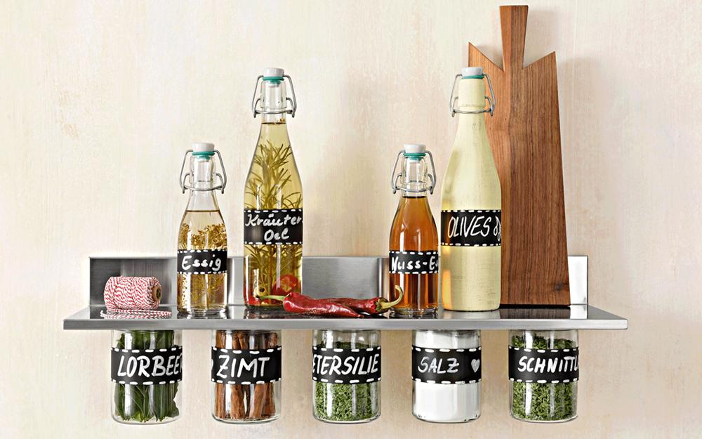 Ein Regal mit Essig & Öl Flaschen und Gläsern.