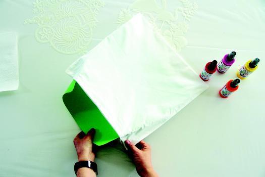 Eine Kartoneinlage wird in eine Kissenhülle geschoben.