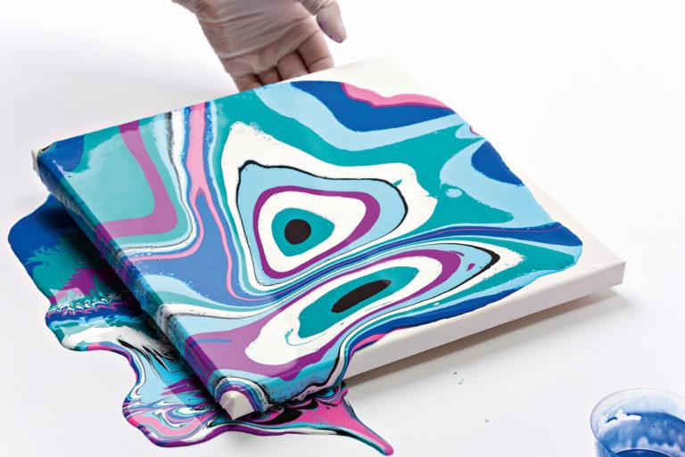 Die flüssigen Farben werden auf dem Keilrahmen hin und her geschwenkt.