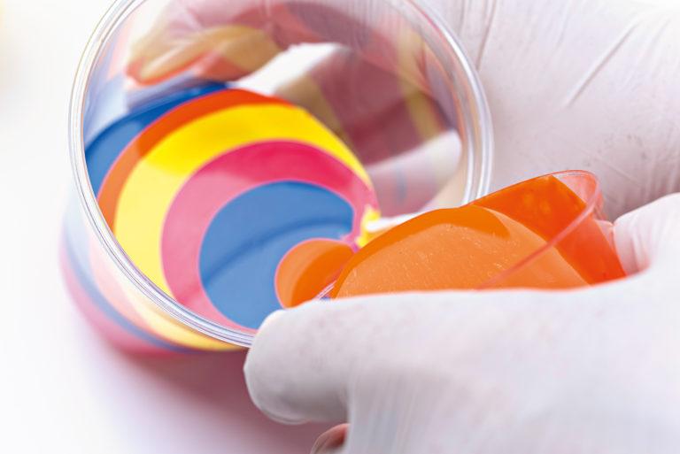 Farben werden in einem Mischbecher übereinander gegossen.