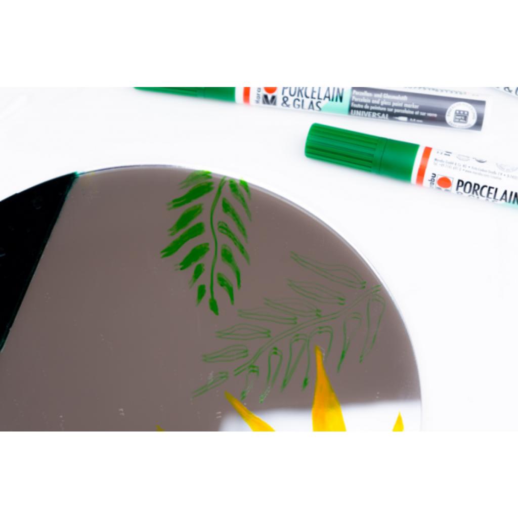 Ein Grasmotiv wird auf den Spiegel aufgezeichnet.