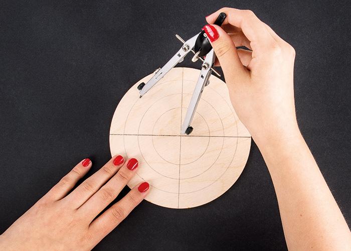 Mit einem Zirkel werden Ringe auf die Holzplatte vom Spiegel aufgezeichnet.