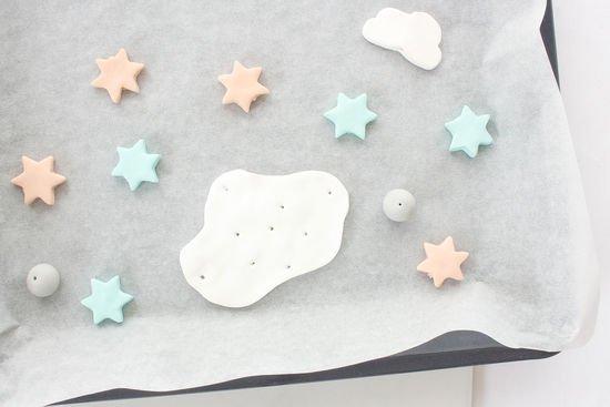 Fimo Wolken, Sterne und Kugeln liegen auf einem Backblech.