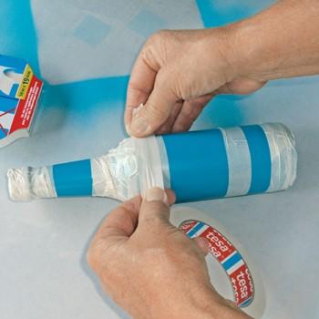 Eine Flasche wird mit Klebeband abgeklebt.