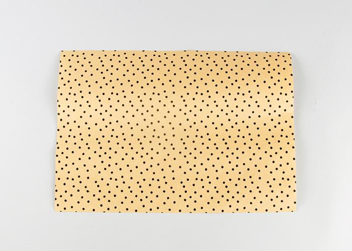 1 Bogen Papier wird für eine Geschenktüte zugeschnitten.