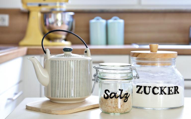 Beschriftete Salz und Zucker stehen mit einer Teekanne auf einem Tisch.