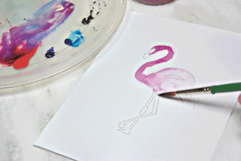 Ein Flamingo wird mit Aquarelltinte gemalt.