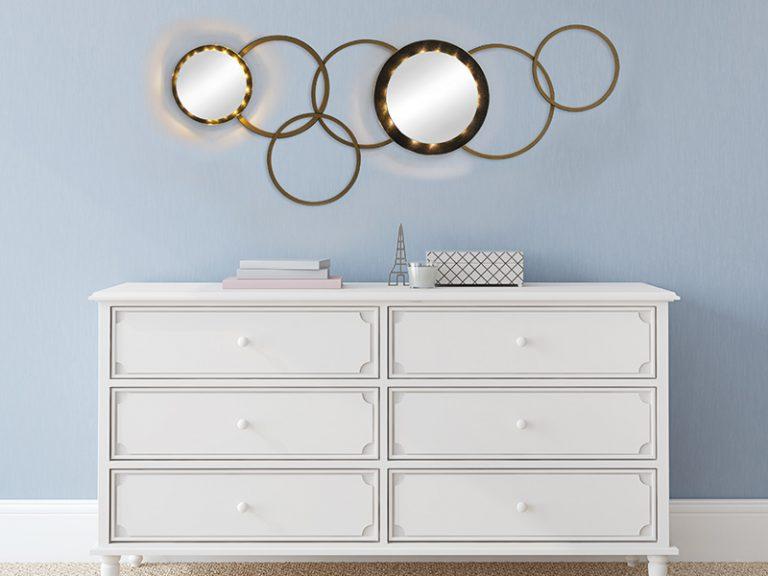 2 Spiegel kombiniert mit Holzringen über einer Kommode.