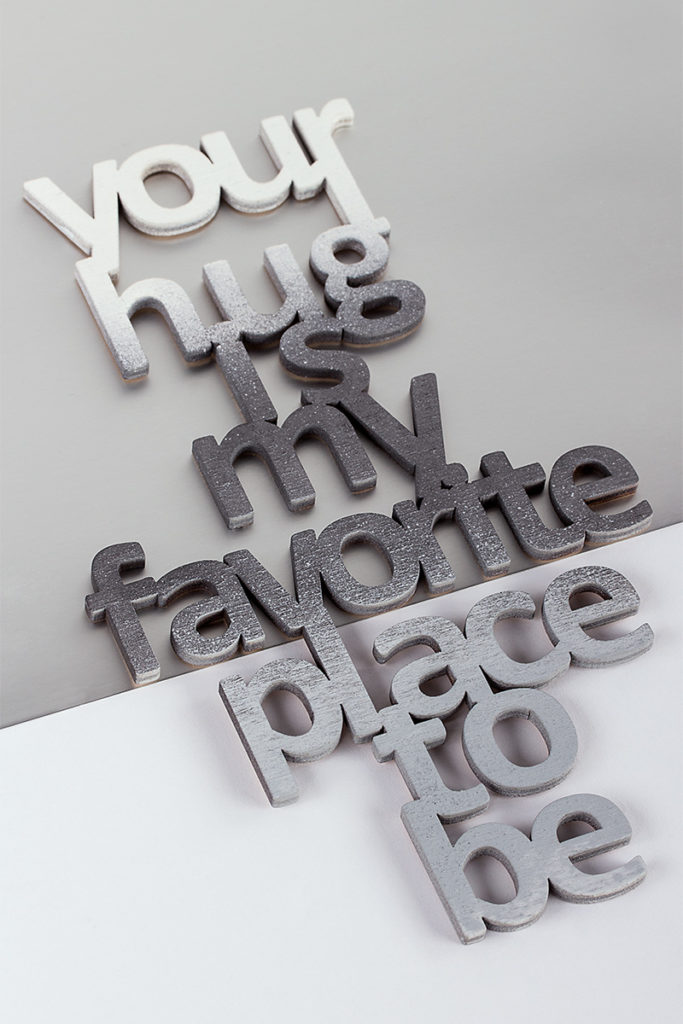 Ein Deko-Holzschild mit dem Spruch Your hug is my favorite place to be""