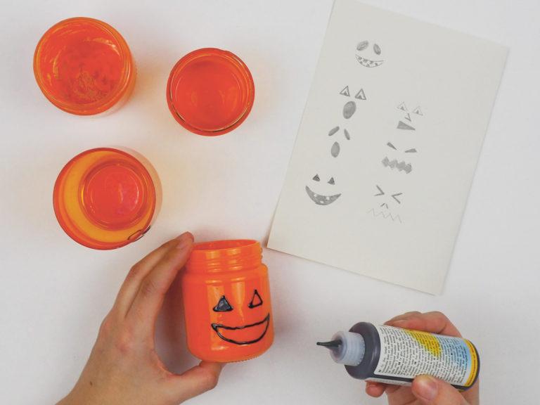Gesichter werden auf die Halloween-Lichter aufgetragen.