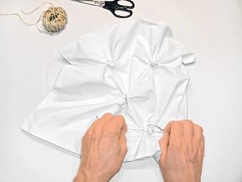 Eine weiße Kissenhülle wird abgebunden.