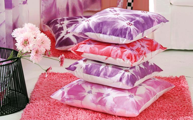 Ein Stapel bemalter Kissen in Pink und Rosa.