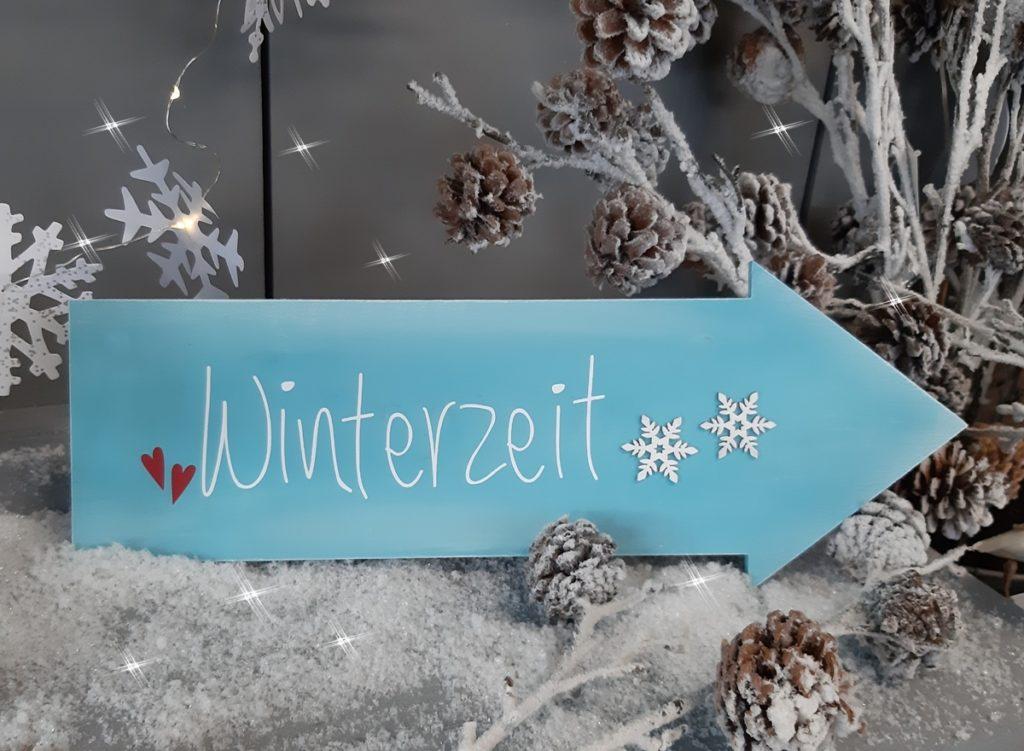 Schild in Pfeilform mit Winterzeit beschriftet.