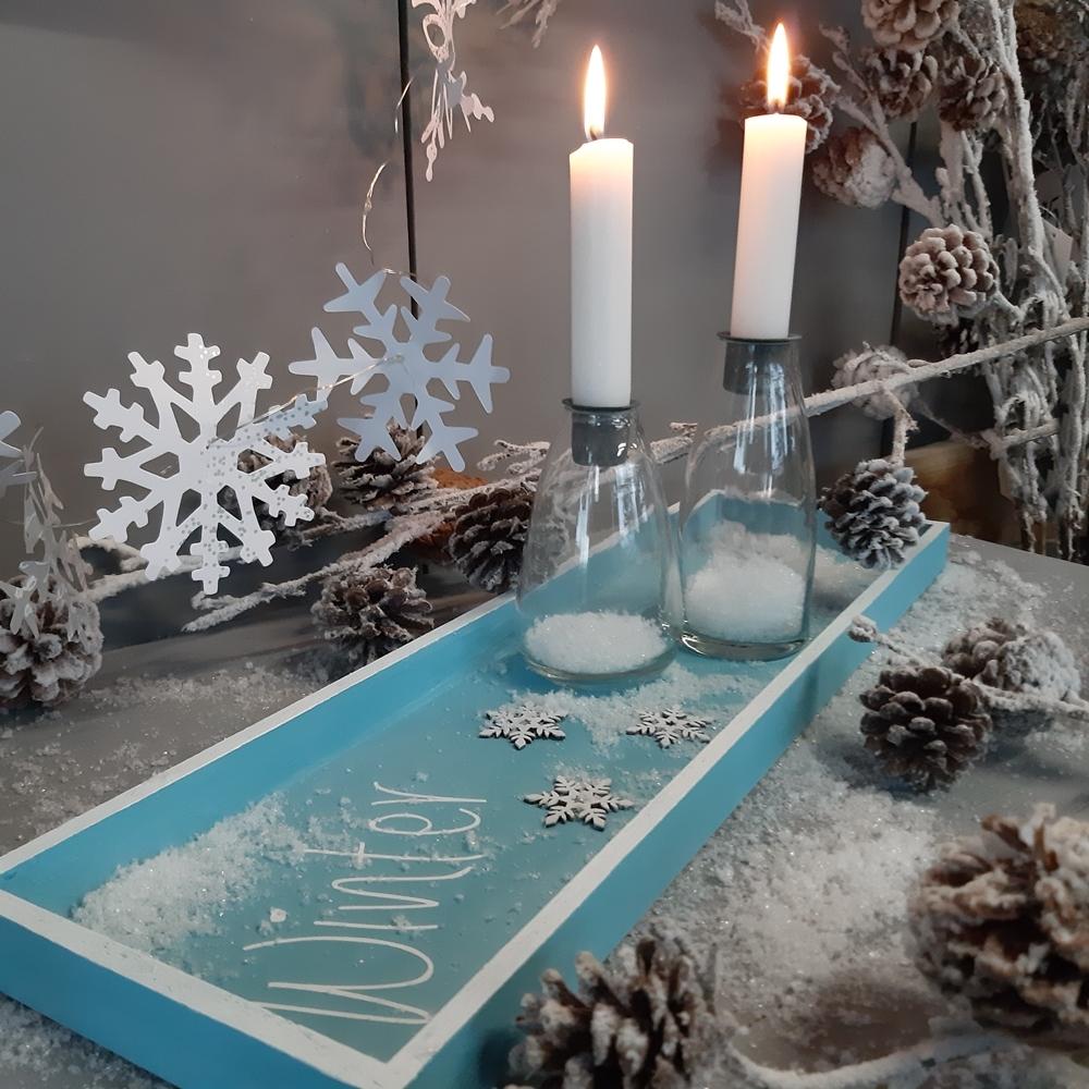 Ein bemaltes Tablett für winterliche Dekorationen.