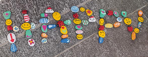 Wort Happy aus bemalten Steinen