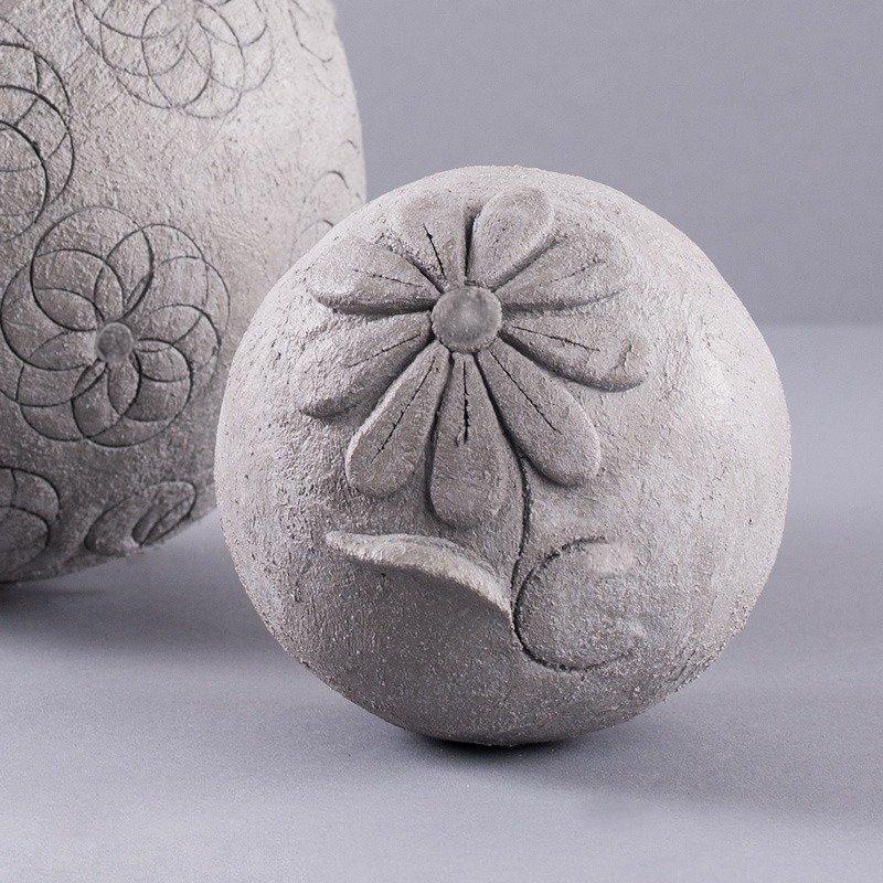 Eine Deko-Kugel aus Knetbeton mit einer Blume.