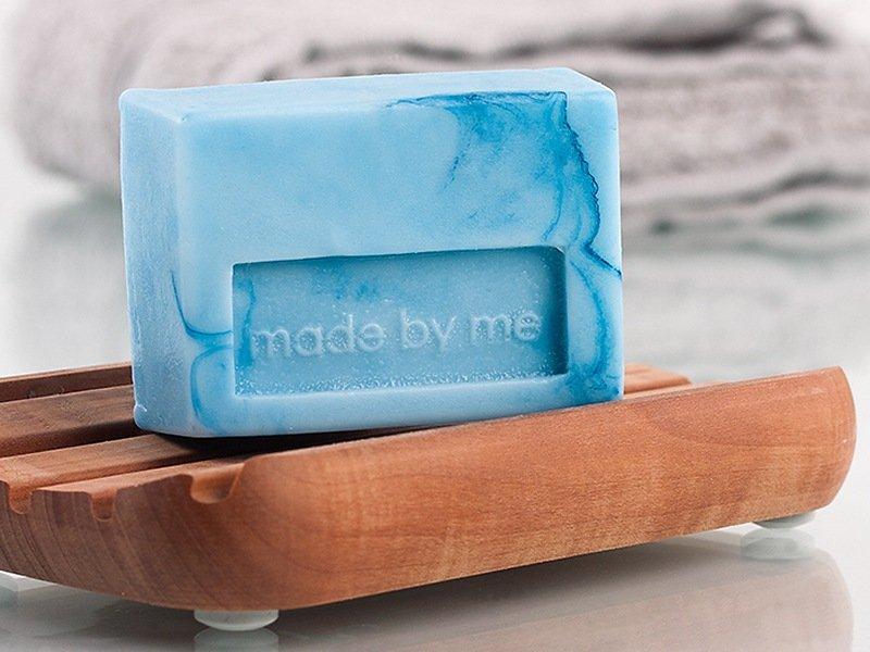 Ein blaues Stück Seife auf einer Ablage.