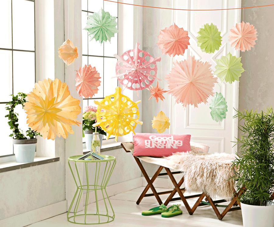 Bunte Blüten aus Papier hängen von der Decke herunter