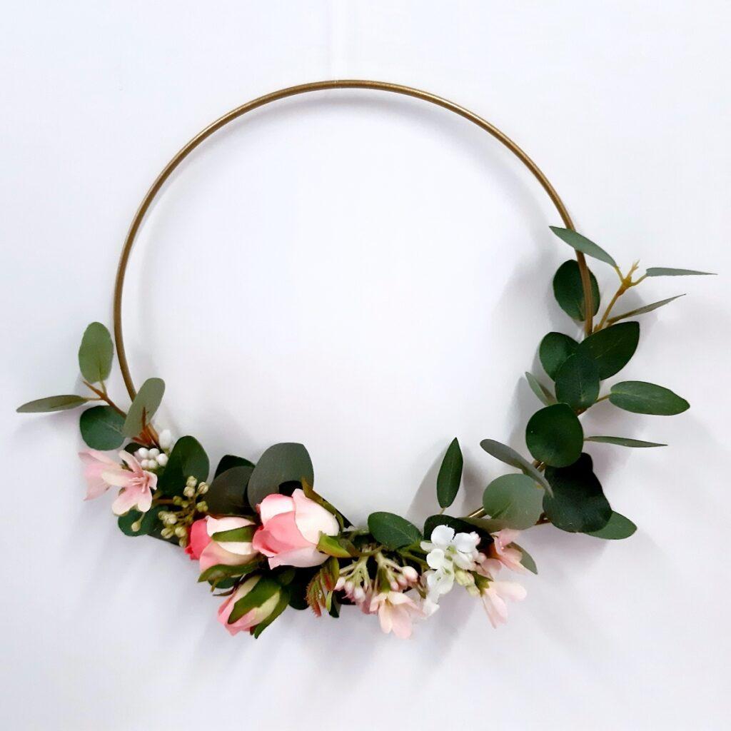 Ein Metallring mit Rosen und Eukalyptuszweigen.