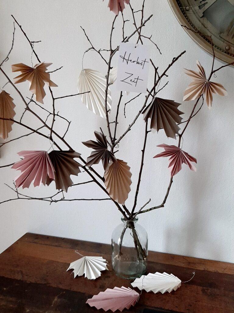 Eine Glasvase mit einem Zweig und gefalteten Blättern.