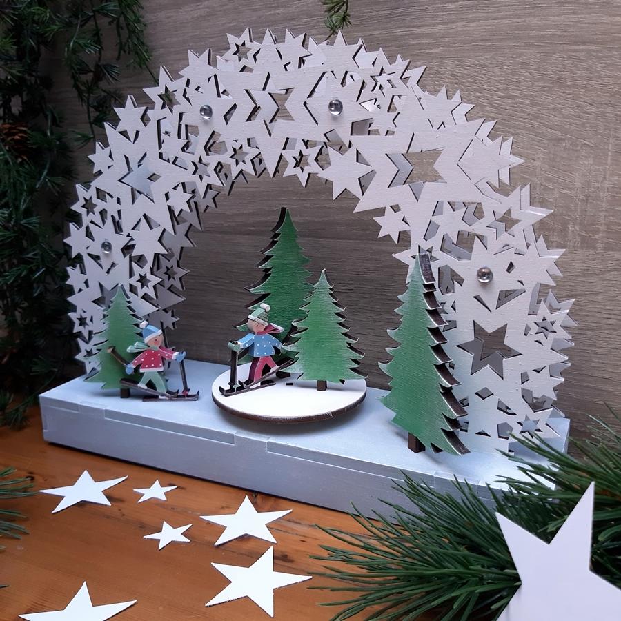 Eine winterliche Szene aus Holz mit einem Sternenhimmel und Skifahrer.