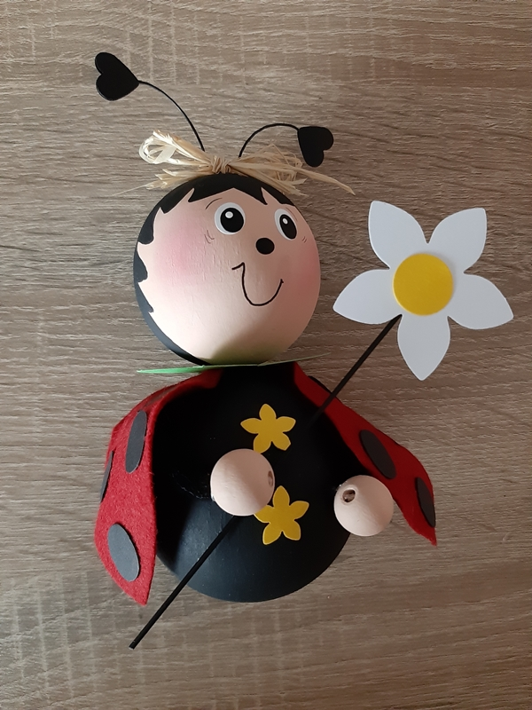 Ein Marienkäfer aus Holzkugeln und Filz