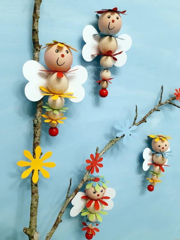 Vier bunte Schmetterlinge aus Holzkugeln und ausgestanzten Blumen