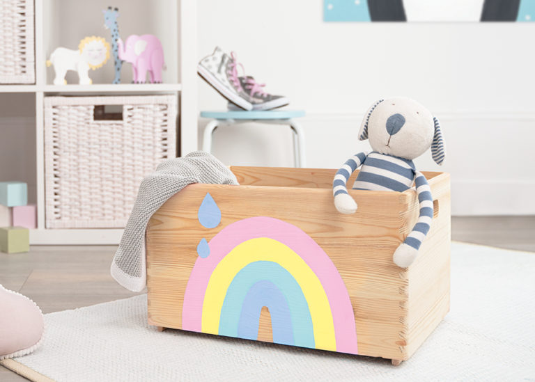 Eine Holzkiste mit einem Regenbogen in Pastellfarben