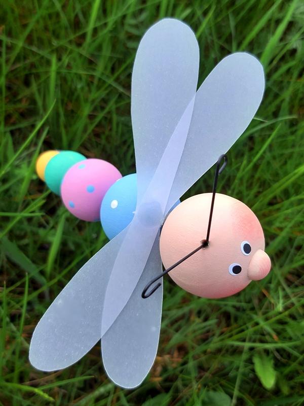 Eine Libelle aus Holzkugeln über einer Grasfläche