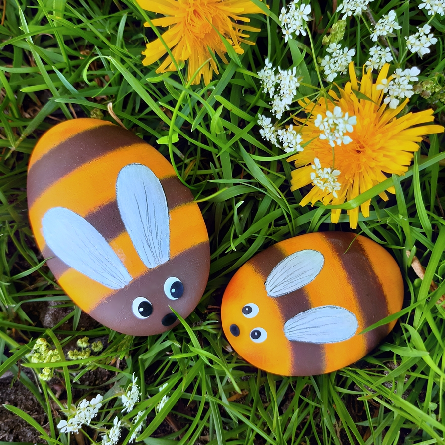 2 Bienen aus bemalten Steinen im Gras