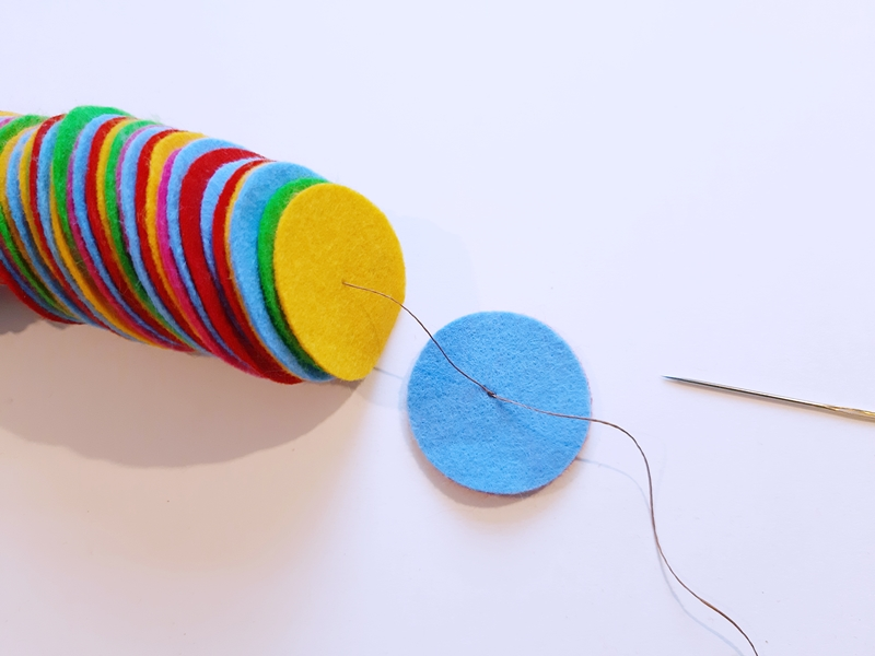 Kreise aus Filz werden mit einem Faden  verknotet
