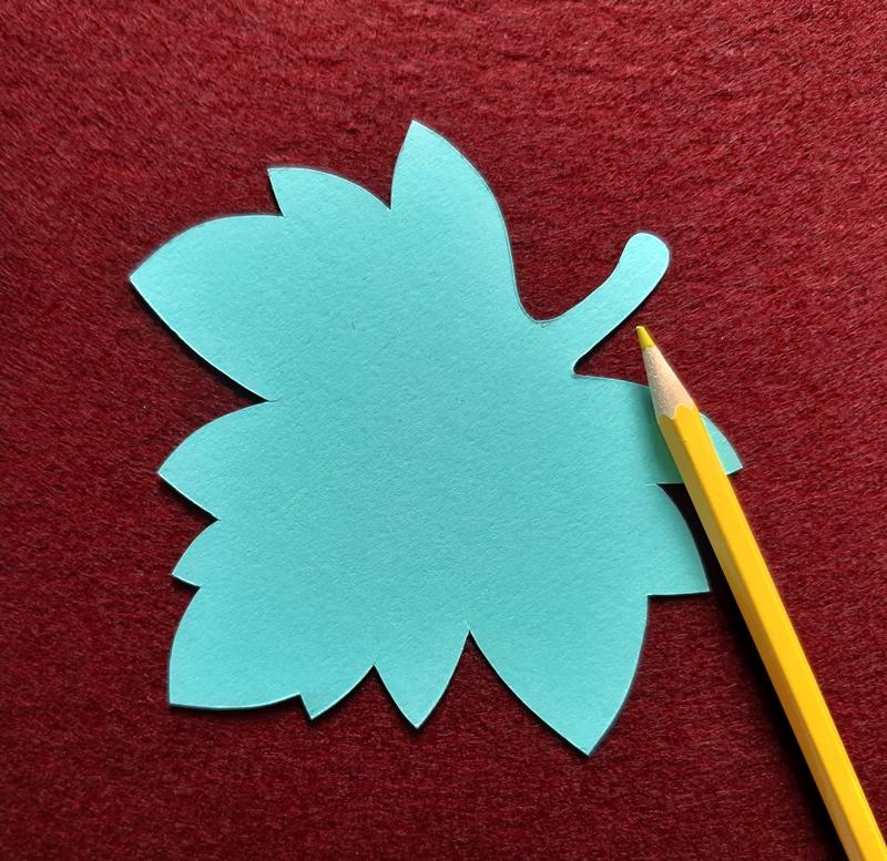 Eine Schablone von einem Ahornblatt liegt zum Abzeichnen auf einem Bogen Filz