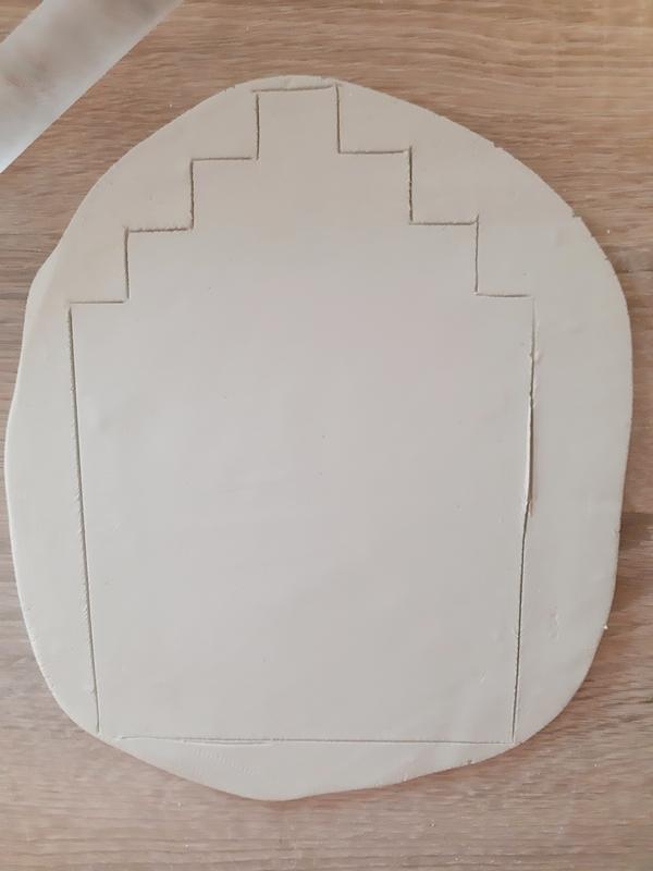 Die Form eines Hauses wird in die Modelliermasse geritzt